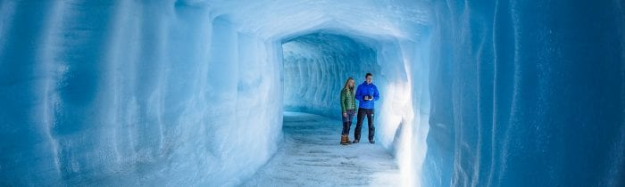 Couple exploring man made ice cave in Iceland