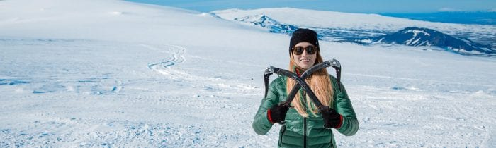 Girl holding ice axes on glacier in Iceland