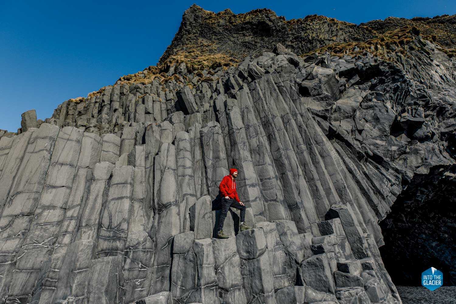 Traveler in red clothes climbed on basalt columns on Reynisfjara beach in Iceland