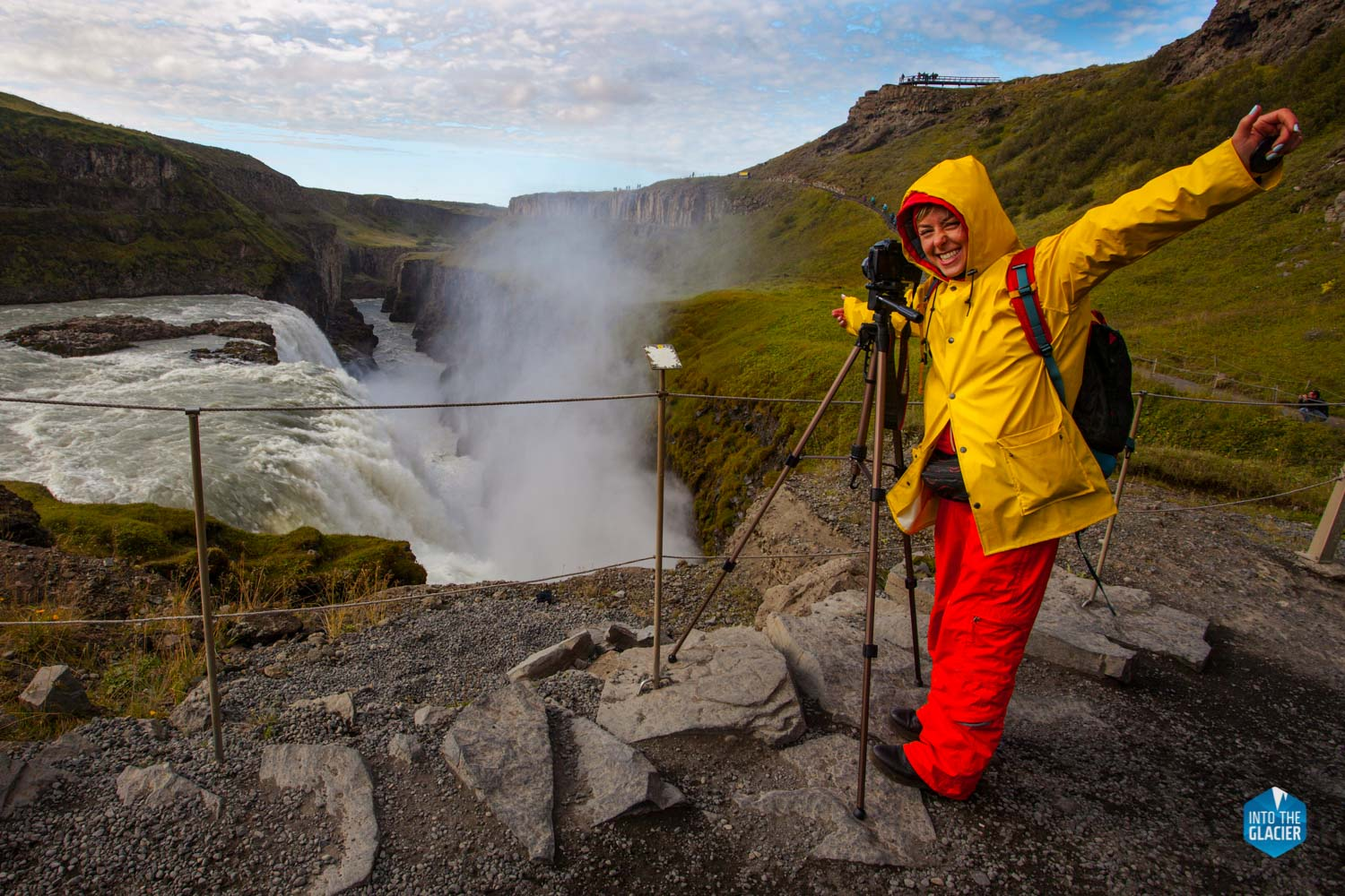 Woman photographer taking picture of Gullfoss waterfall